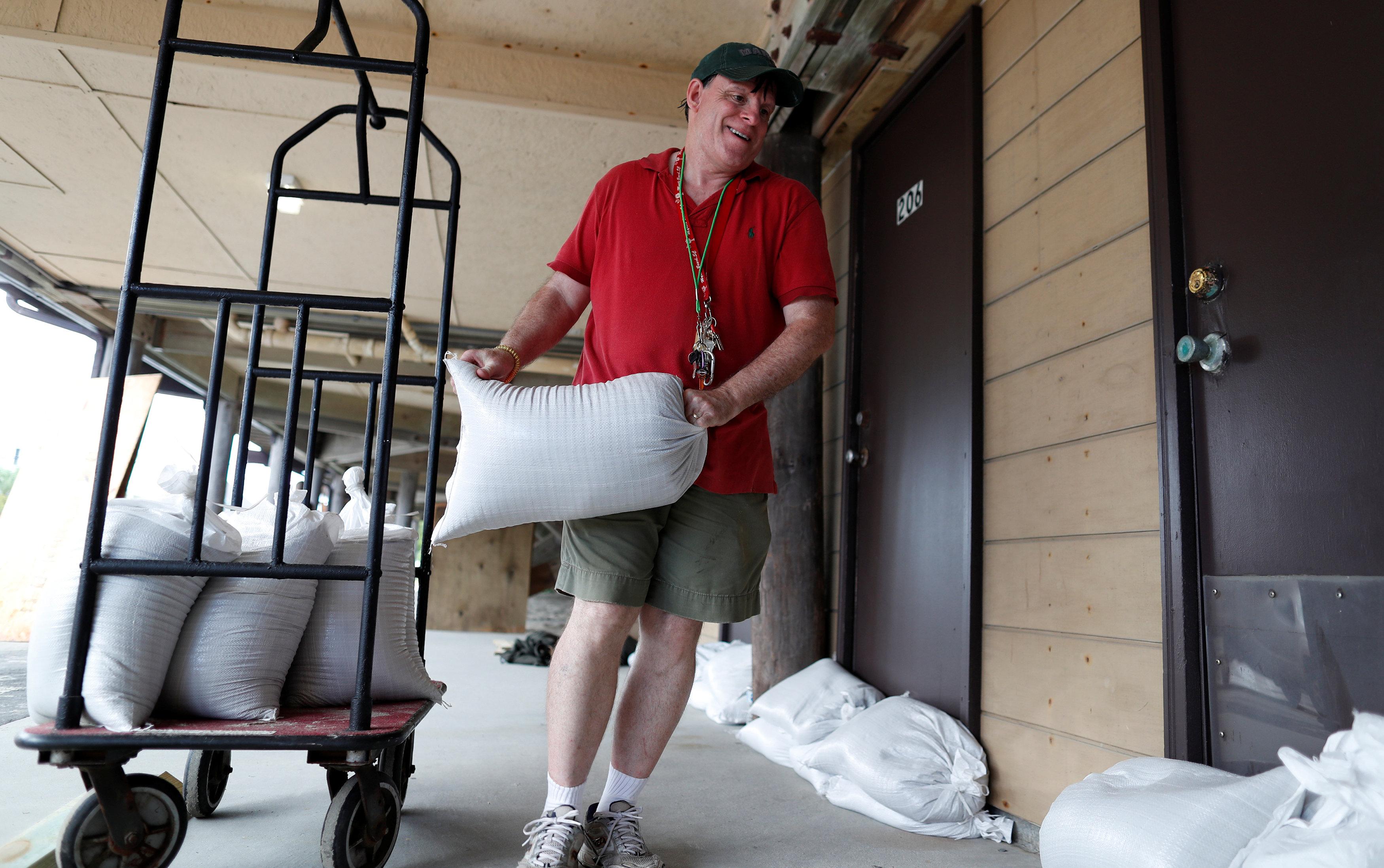 Habitantes colocan costales de arena en las puertas de sus casas para evitar el paso del agua por las lluvias que provoca el huracán.