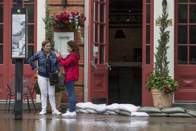 Los dueños de comercios colocan costales llenos de arena en las puertas ante las lluvias que provoca Florence.