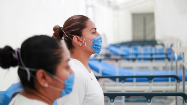 Two nurses wearing protective masks pose inside the new immediate response mobile hospital in Pachuca