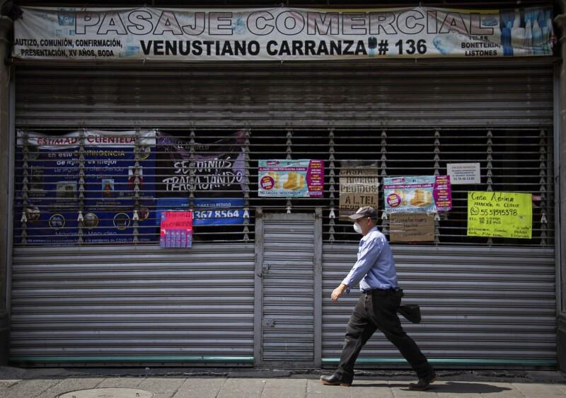 Un hombre camina por la Calle Venustiano Carranaza en el Centro Histórico, frente a el, una plaza cerrada con diversos letreros con invitaciones de los comerciantes a contactarlos vía telefónica