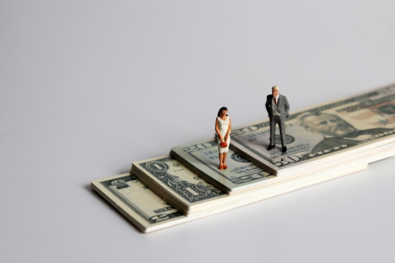 A miniature man and a miniature woman standing on a pile of bills.