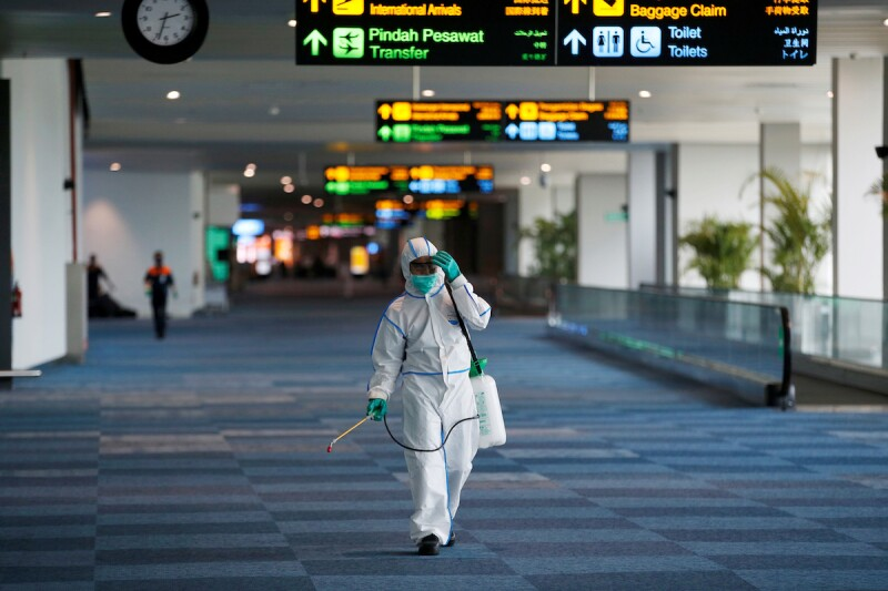 A worker wearing protective suit reacts as he sprays disinfectant at the international arrivals terminal of Soekarno-Hatta Airport