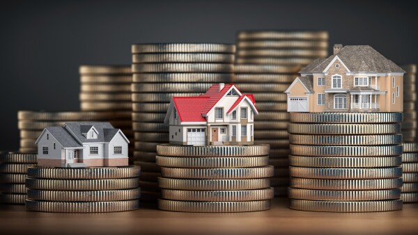 Houses of different size with different value on stacks of coins. Concept of  property, mortgage and real estate investment.