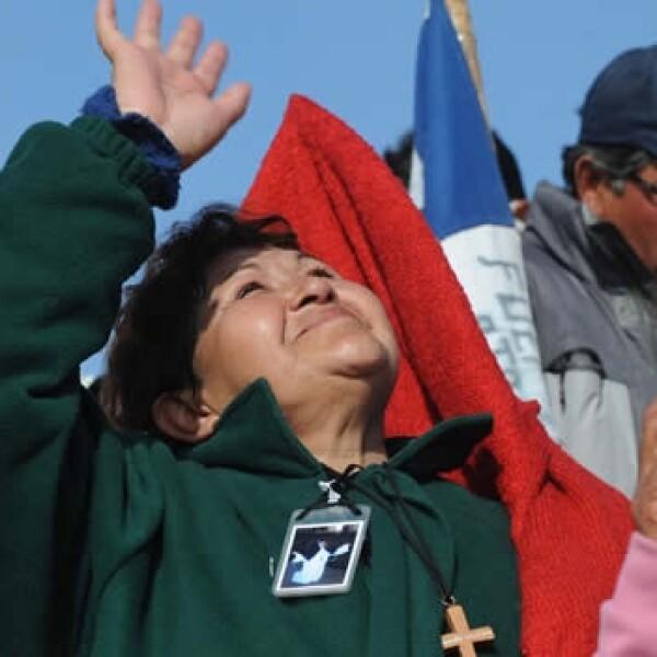 Una de las familiares de los mineros da gracias a Dios con una seña de mano de mano