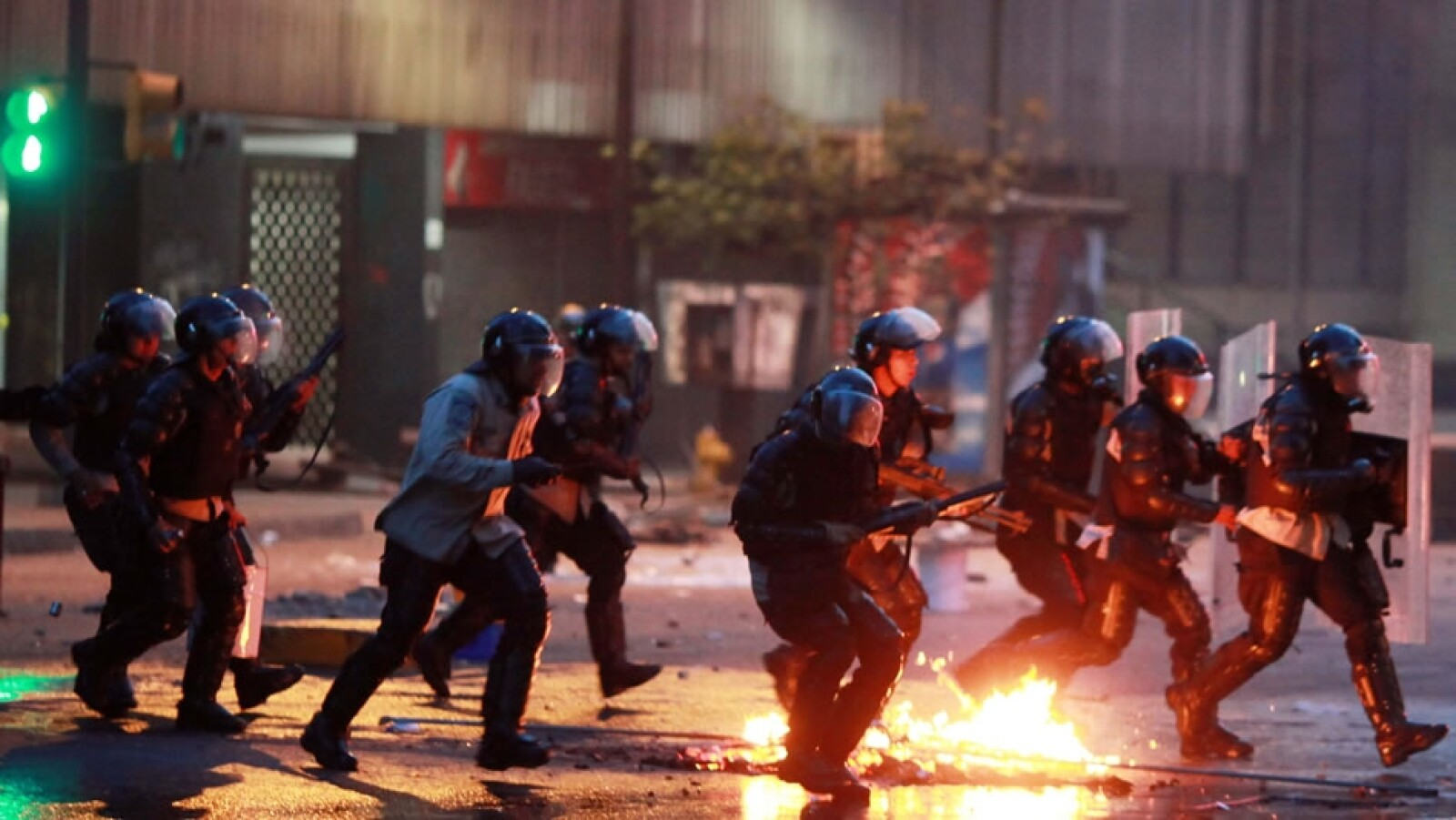 Policías corren tras manifestantes en Caracas este domingo