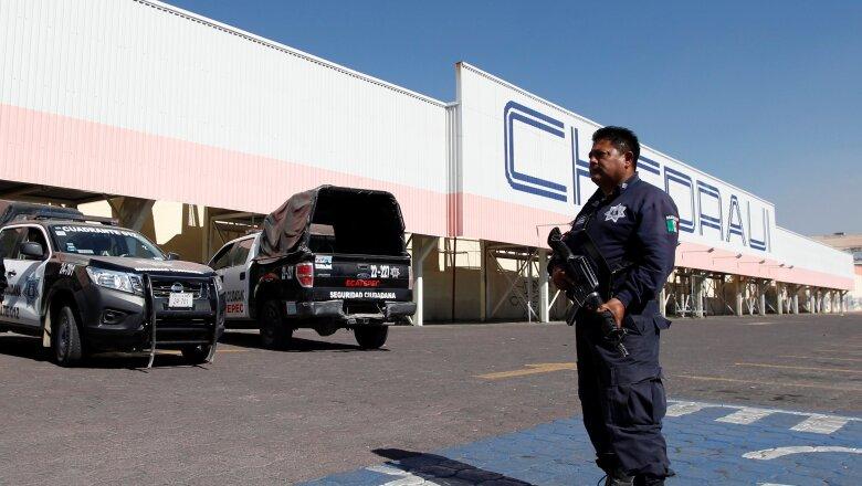 En Ecatepec, la policía resguarda una tienda un día después de ser saqueada.