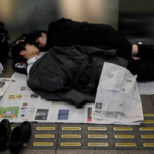 Varias personas duermen en el Tokio International Forum, un centro de espectáculos adaptado como un refugio temporal.