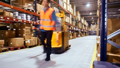 Warehouse, worker with a forklift in motion blur.