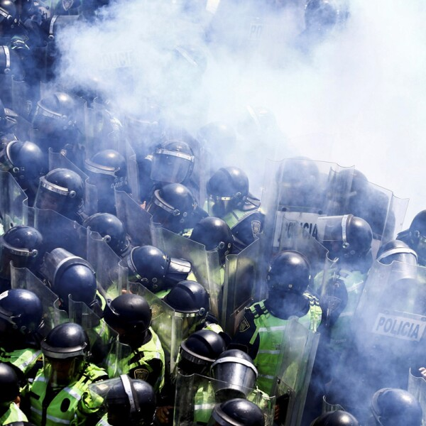 Police officers are pictured amidst tear gas as members of the Federal Police block the access to one of the terminals of Benito Juarez International airport in Mexico City