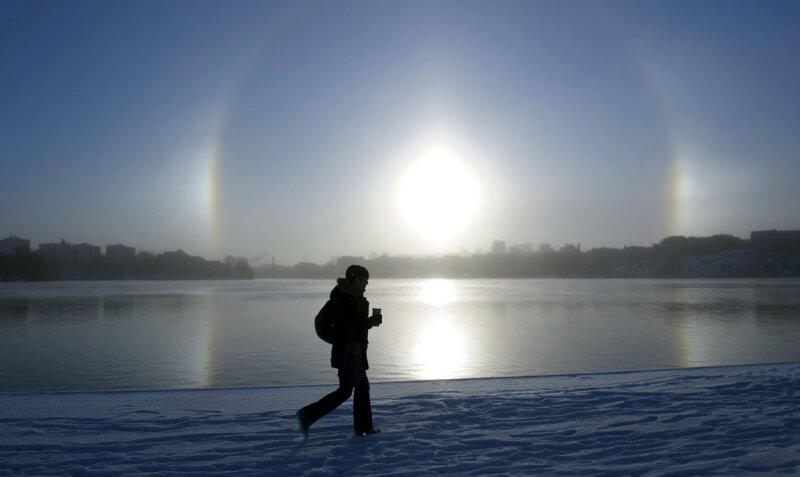 Una mujer pasea a orillas del lago Malaren con el fenómeno atmosférico Parhelio visto al fondo