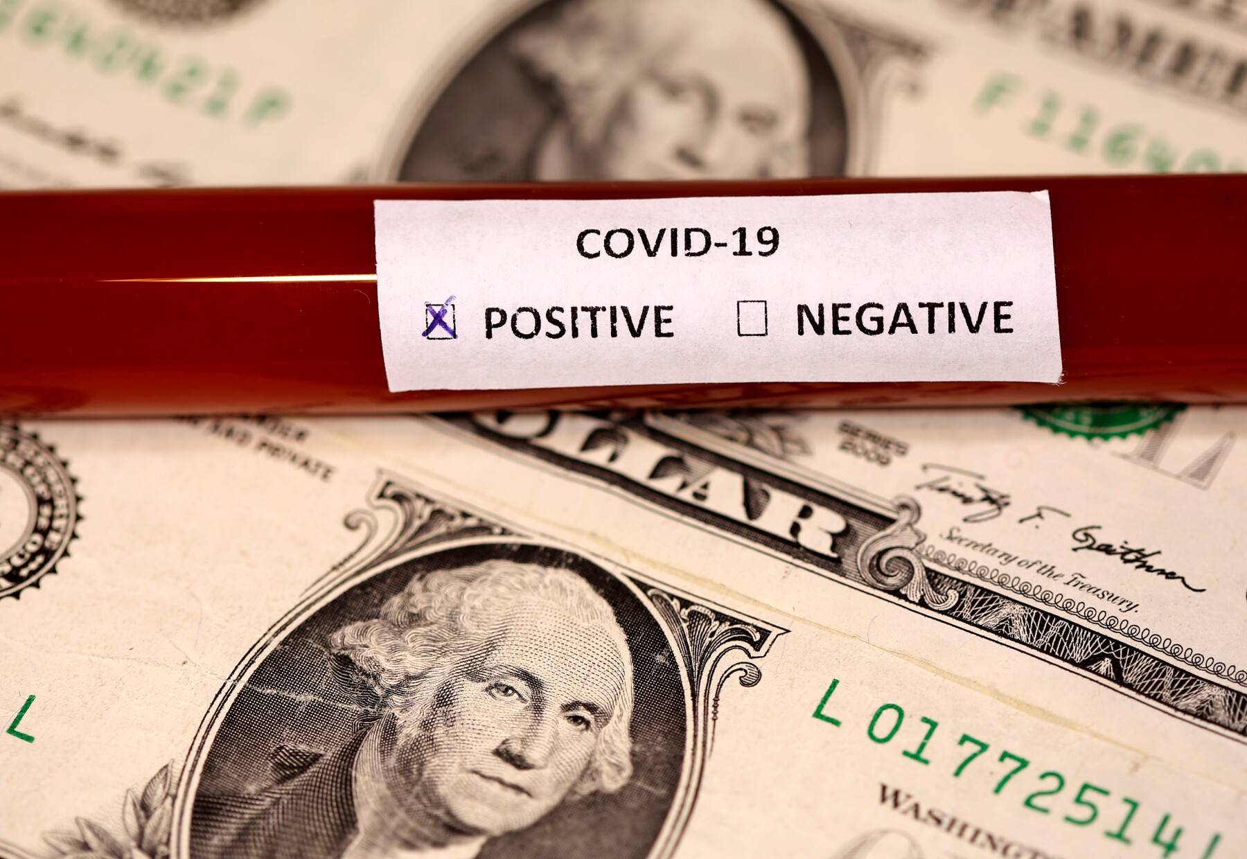 FILE PHOTO: Picture illustration of a test tube labelled with the coronavirus placed on U.S. dollar banknotes