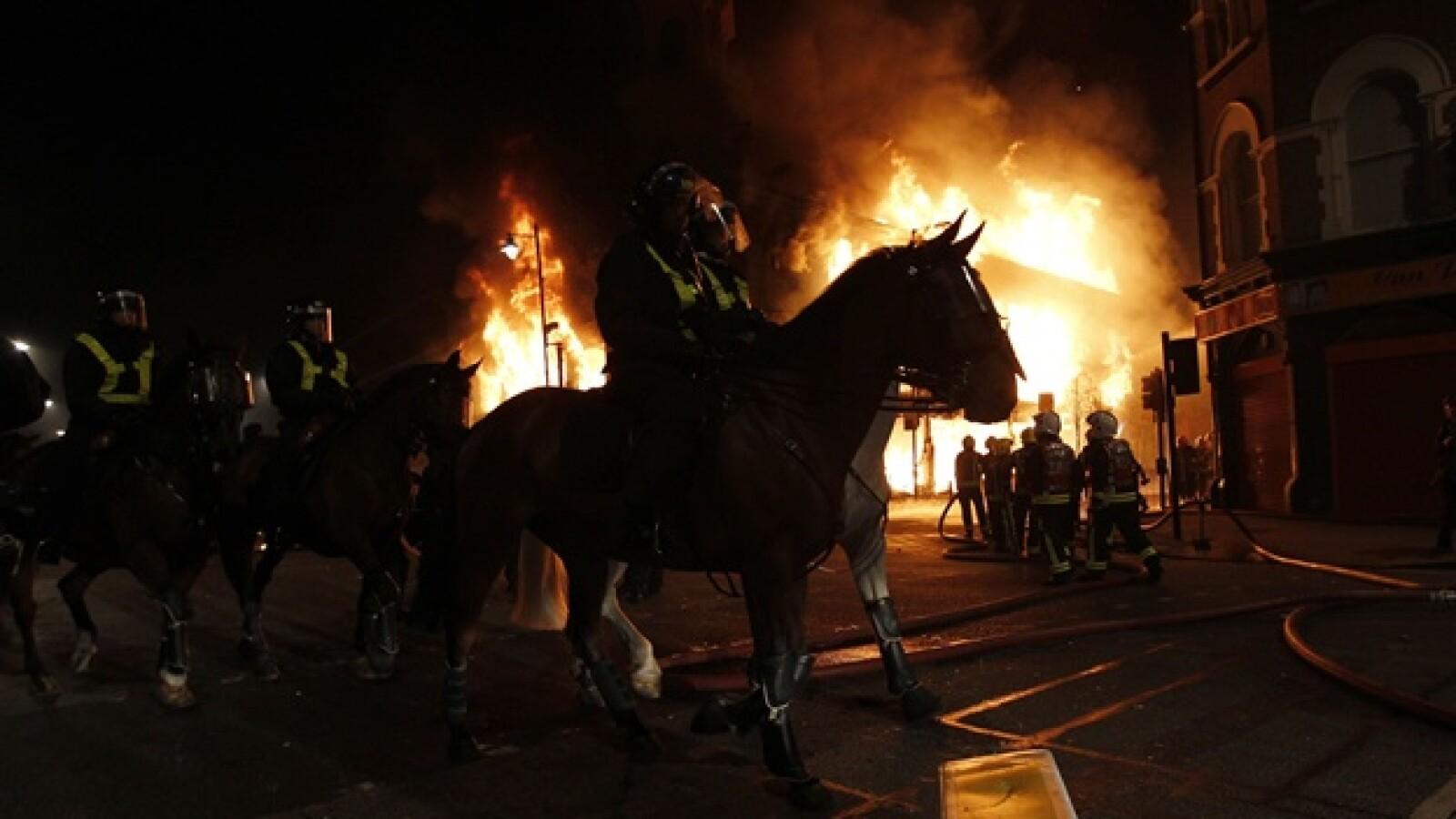 polica montada de londres ante edificio incendiado