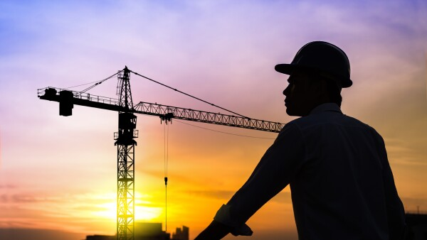 portrait of architect silhouette wear a helmet at construction site with crane background and sunset