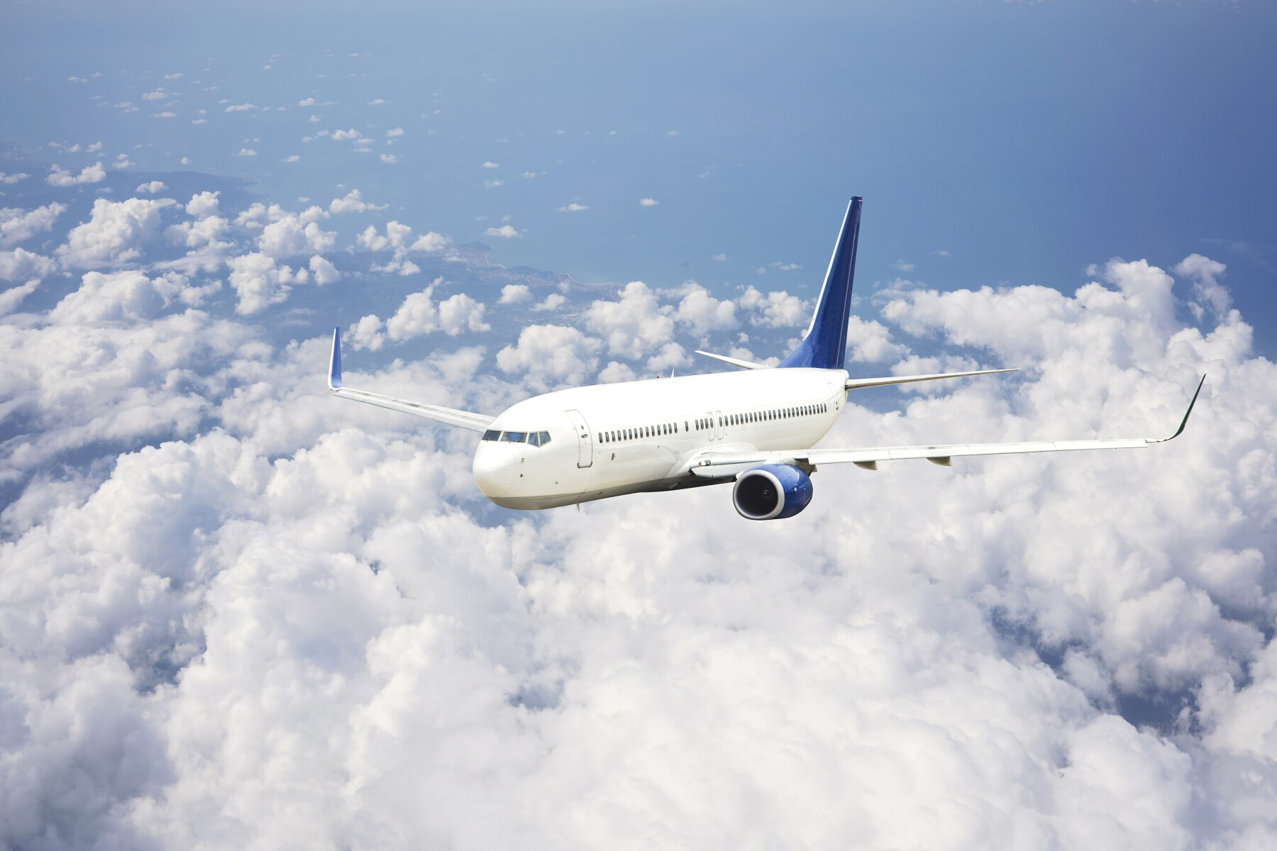 Passenger jet airplane flying above clouds.