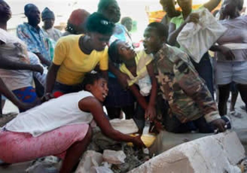 En la foto se muestra cómo haitianos pelean por comida y otros bienes tomados de una tienda derrumbada en Puerto Príncipe. (Foto: AP)