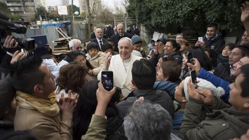 El papa Francisco es saludado por habitantes de un barrio pobre de Roma este domingo