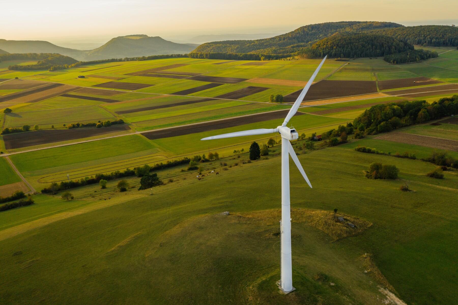 Alternative Energy Wind Turbine in Beautiful Green Landscape at Sunset