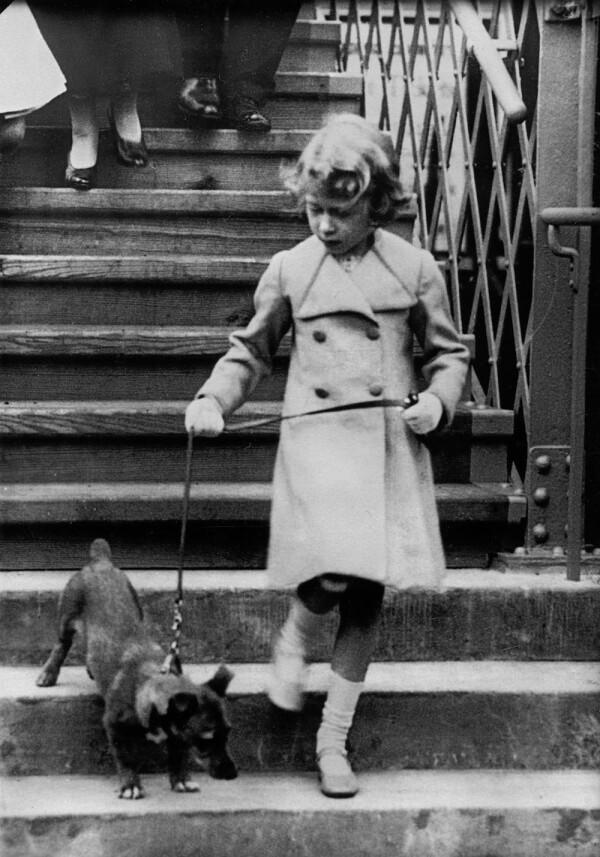 Princess Elizabeth of England takes her dog for a walk. Photograph. Around 1931.