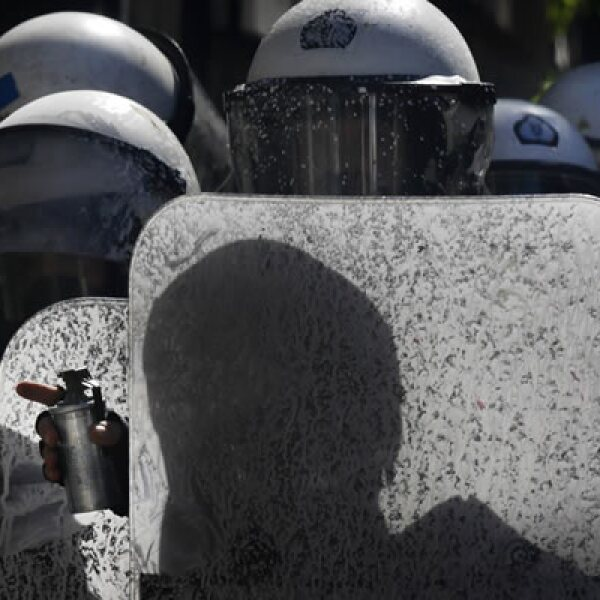 Policías antidisturbios se protegen, mientras preparan las granadas de gas lacrimógeno durante los enfrentamientos.