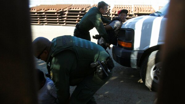 U.S. border patrol officers detain a group of migrants after they entered the United States illegally by jumping over the border fence between Mexico and the United States, from Tijuana