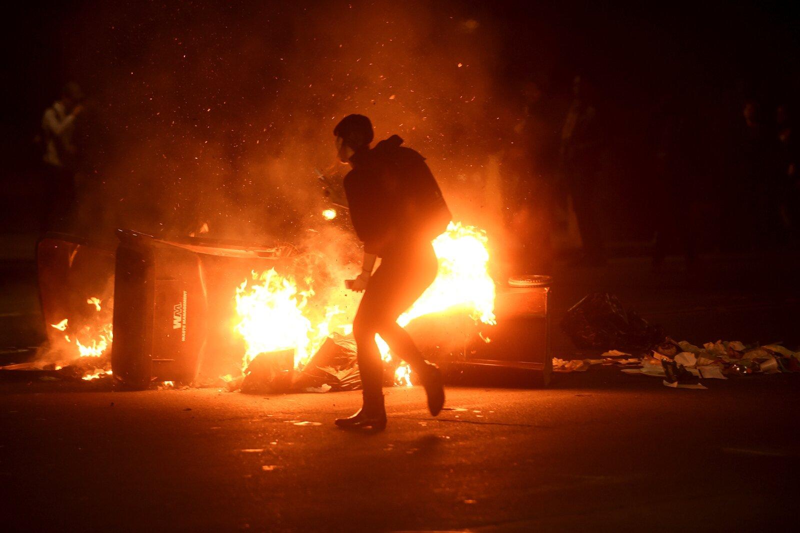 Una mujer pasa la basura ardiendo en Oakland, California