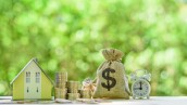 Mortgage-backed security MBS, financial concept : House model, stacks of rising coins, US dollar, money bags, a clock on a table over green background, depicts investment in home bought from the bank