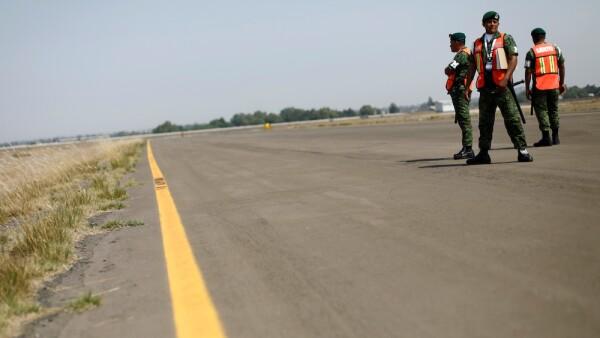 Soldiers keep watch on a landing strip at Santa Lucia military airbase during Aerospace Fair 2019 in Tecamac
