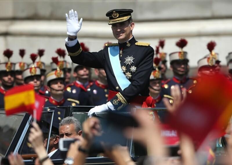 Desde un descapotable, Felipe VI saluda a la multitud que lo esperaba en las calles de Madrid.