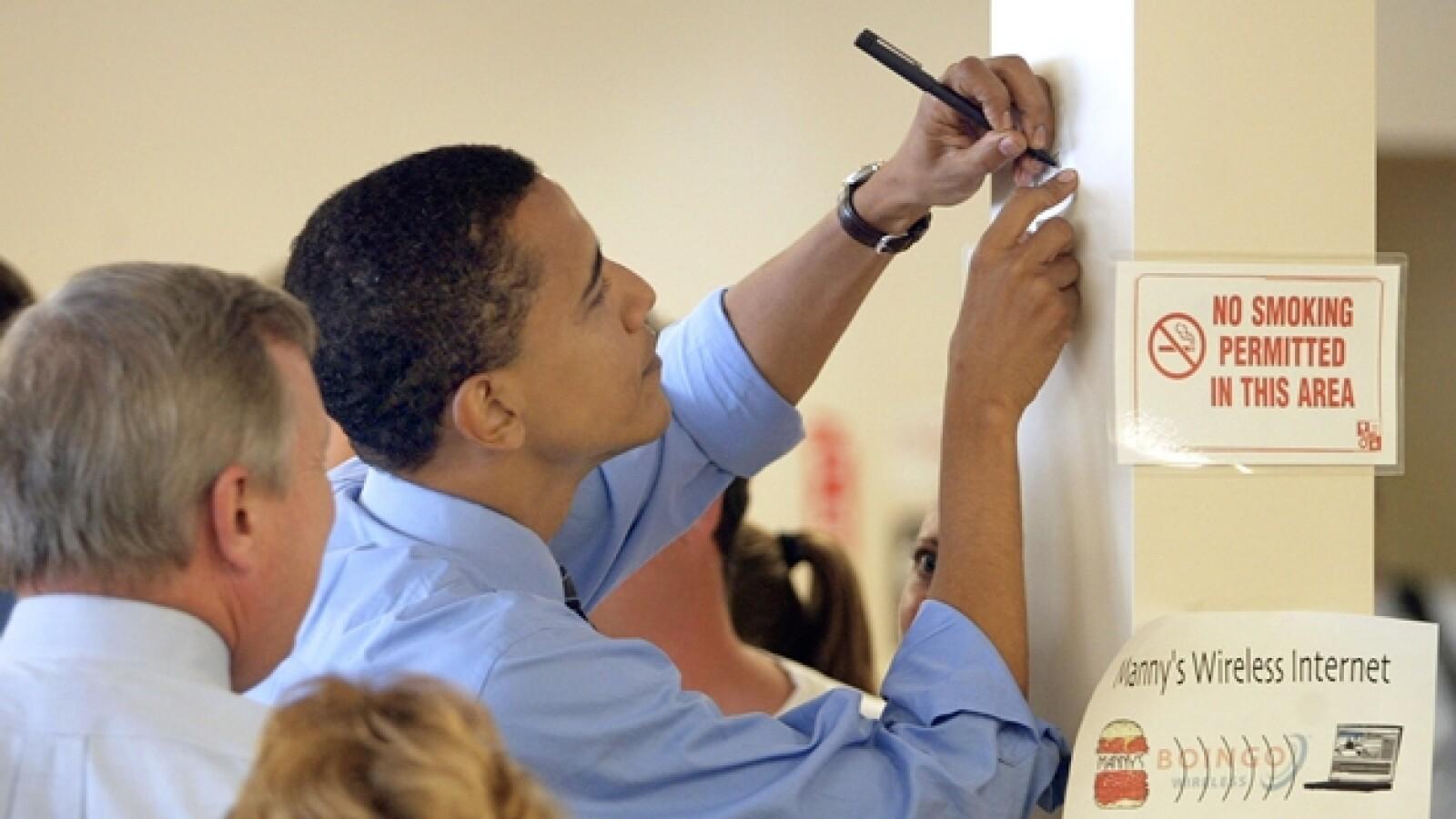 obama escribe en un muro con la mano izquierda