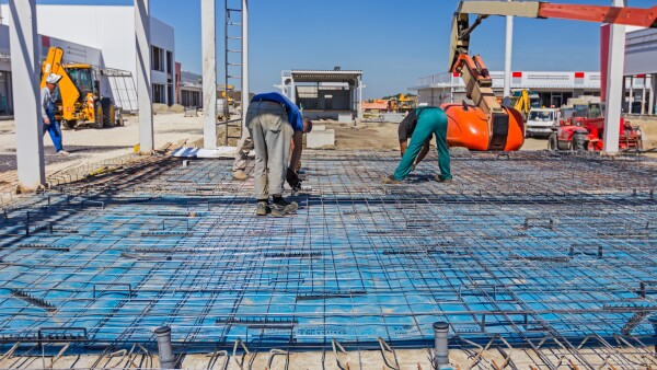 Workers are installing reinforcement mesh manually.