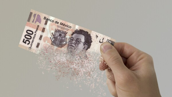 Mexican Pesos bill pulverizes in a man's hand.