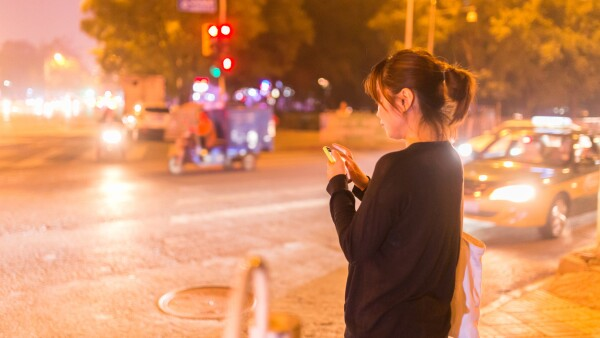 girl ordering taxi through phone at night