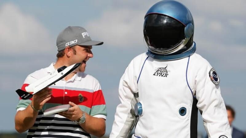 El golfista inglés Andy Sullivan festeja junto a un ?astronauta? su hoyo en uno y viaje al espacio