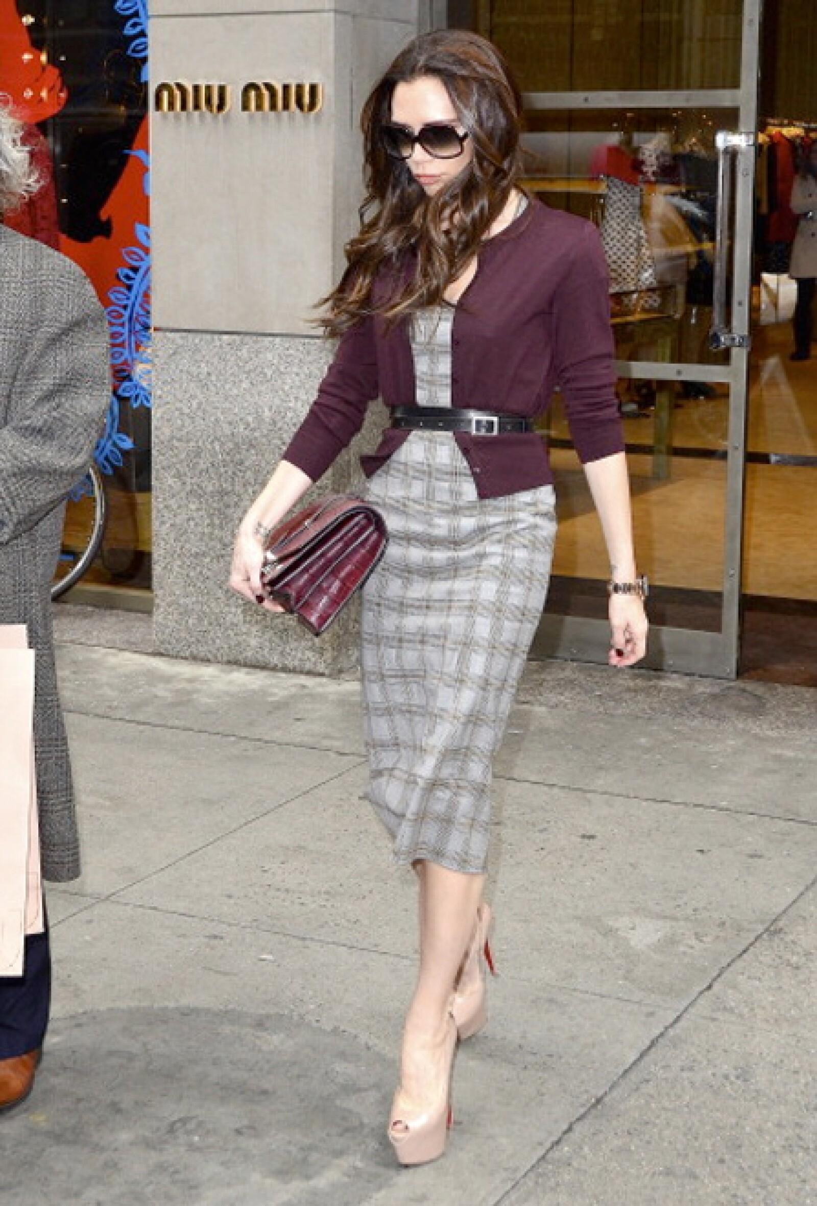 Victoria Beckham accesoriza un vestido con un suéter abotonado y un cinturón.
