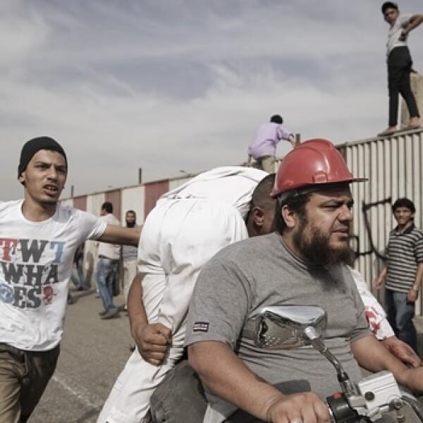 manifestantes llevan a un herido en moto