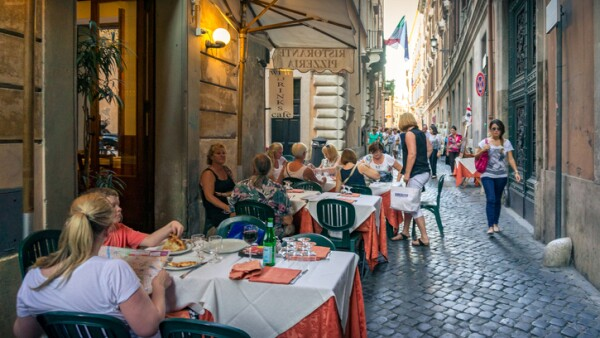 People and families sitting in outdoor dinning area in Italian restaurant