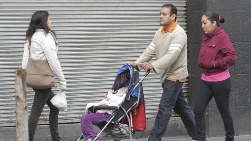 personas caminan en la calle con sueteres