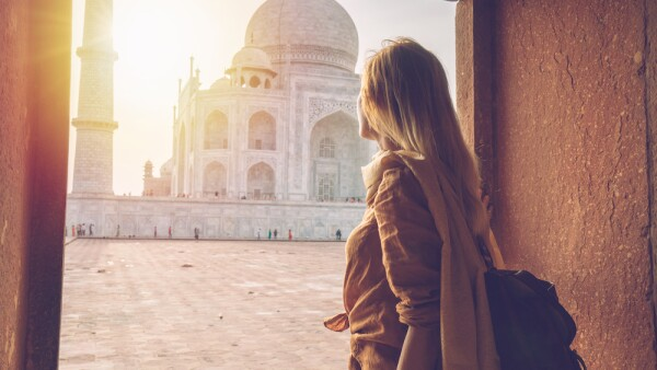 Beautiful blond hair girl contemplating sunrise at the Taj Mahal in India