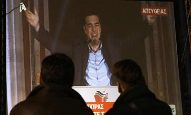Personas observan al líder de Syriza dando un discurso luego de ganar las elecciones en Atenas. (Foto: Reuters )