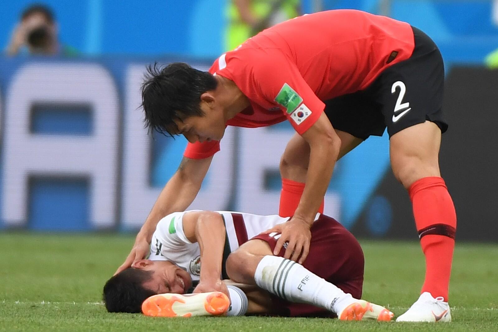 El surcoreano Lee Yong asiste al mexicano Hirving Lozano tras una falta