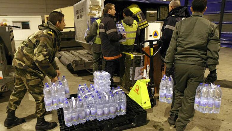 Miles de toneladas de comida, agua y medicamentos han empezado a llegar al aeropuerto de la ciudad de Puerto Principe. En la foto, bomberos franceses se alistan para ayudar descargando agua y otros alimentos.