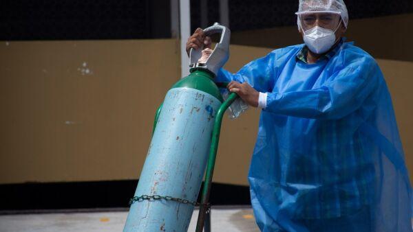 Un médico lleva un tanque de oxígeno al Triage del Hospital General de México.