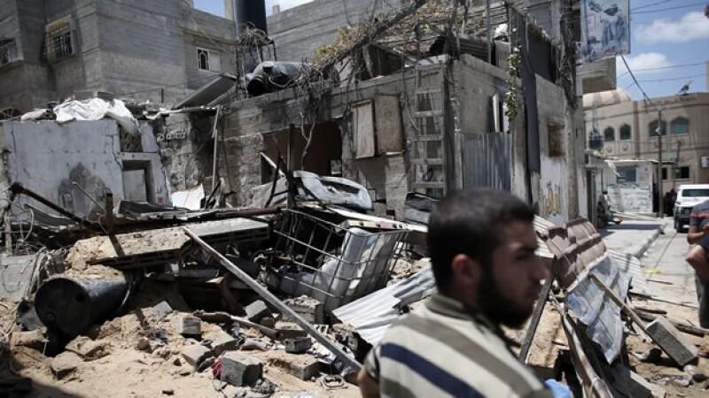Un integrante de Hamas se mantiene alerta frente a un edificio destruido por un ataque aéreo de Israel este lunes, en Gaza