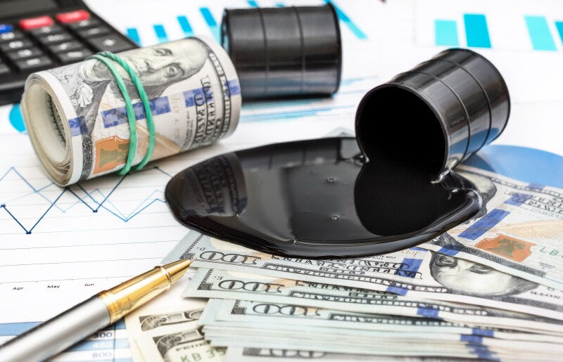 Spilled crude oil with money and calculator on financial graphs.
