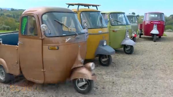 Nostálgicos vehículos de 3 ruedas recorren la campiña toscana en Italia