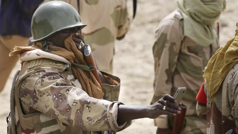 Un soldado toma una foto de los cadáveres encontrados al norte de Nigeria, en un pueblo controlado por Boko Haram