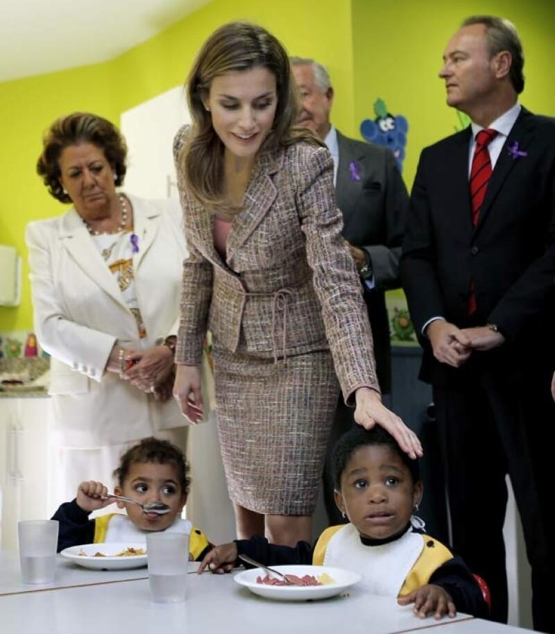 La princesa acarició y demostró afecto a los niños que comían.