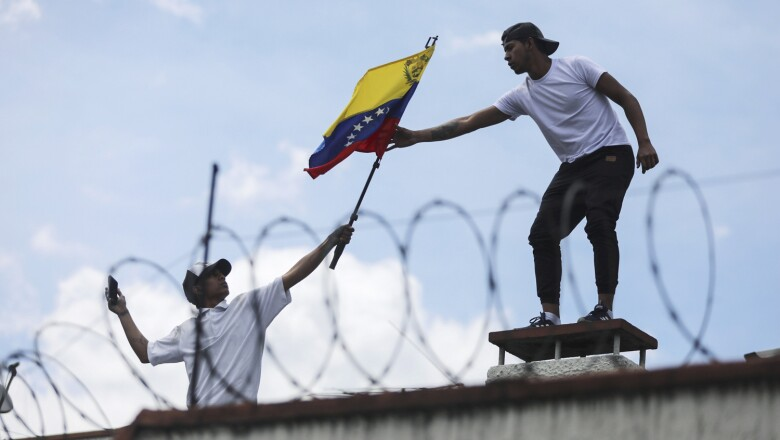 A man gives a flag of Venezuela to one another, on the roof of the Consulate of Venezuela, during a protest in Bogota