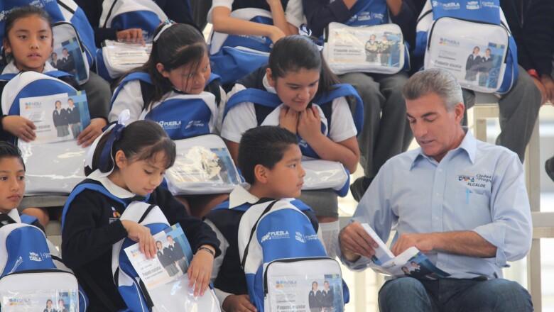 Reunido con estudiantes de primaria, a quienes entregó mochilas con su firma.