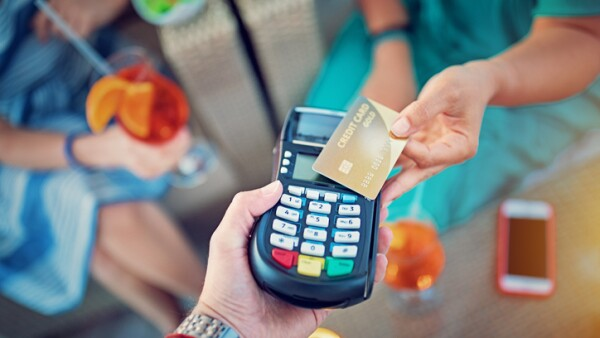 Girlfriends are paying their cocktails on the beach bar using contactless credit card